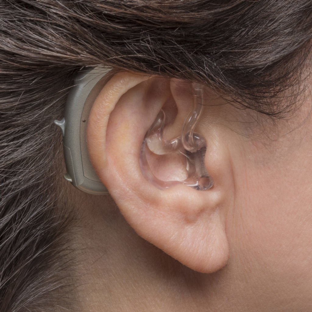 Photo of woman wearing behind the ear (BTE) hearing aid
